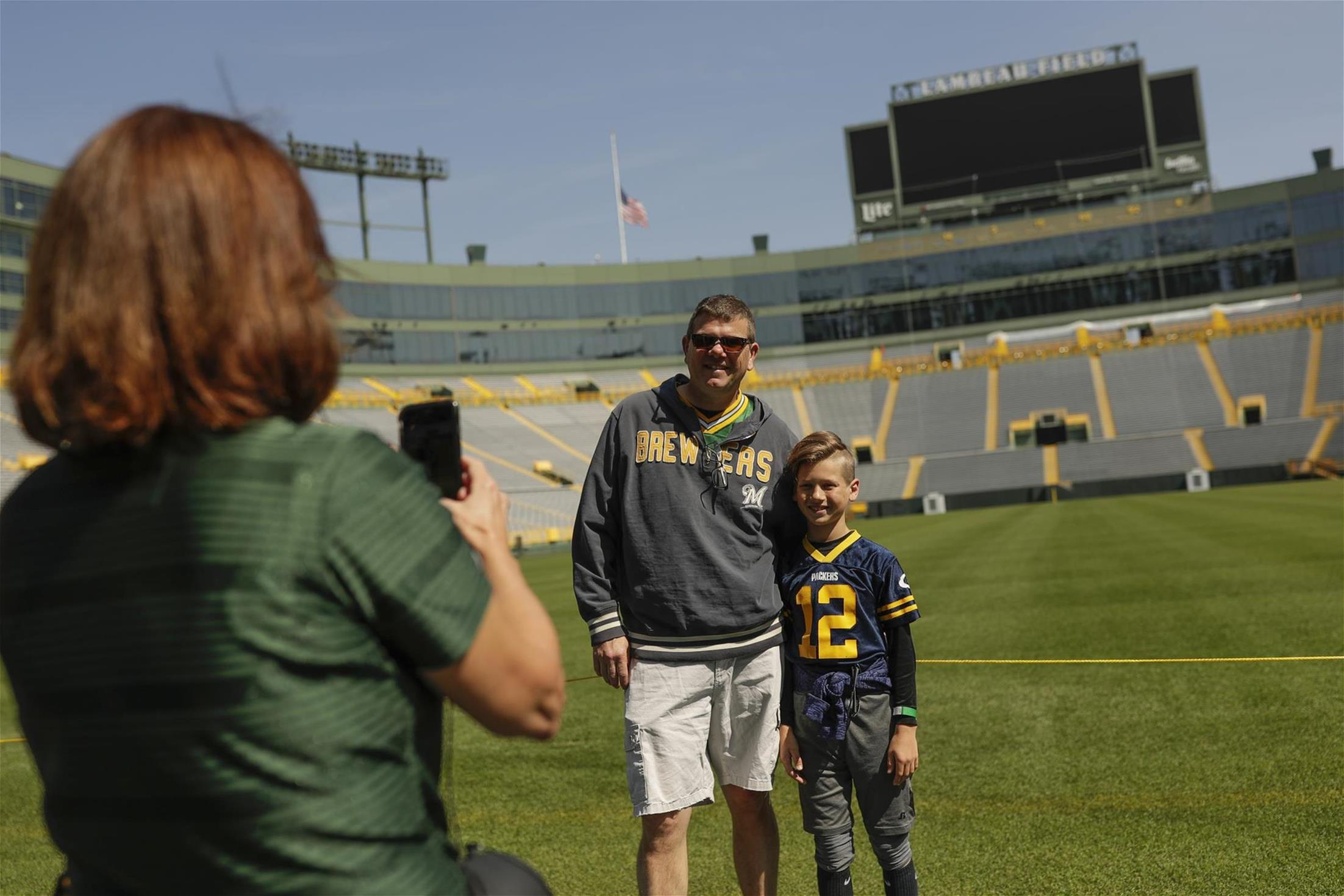 Tour guide taking a photos of guests near Lambeau Field on a stadium tour.